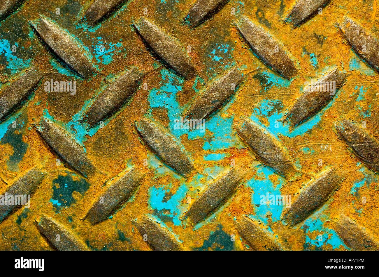 Turquoise paint on rusted patterned metal. - Stock Image