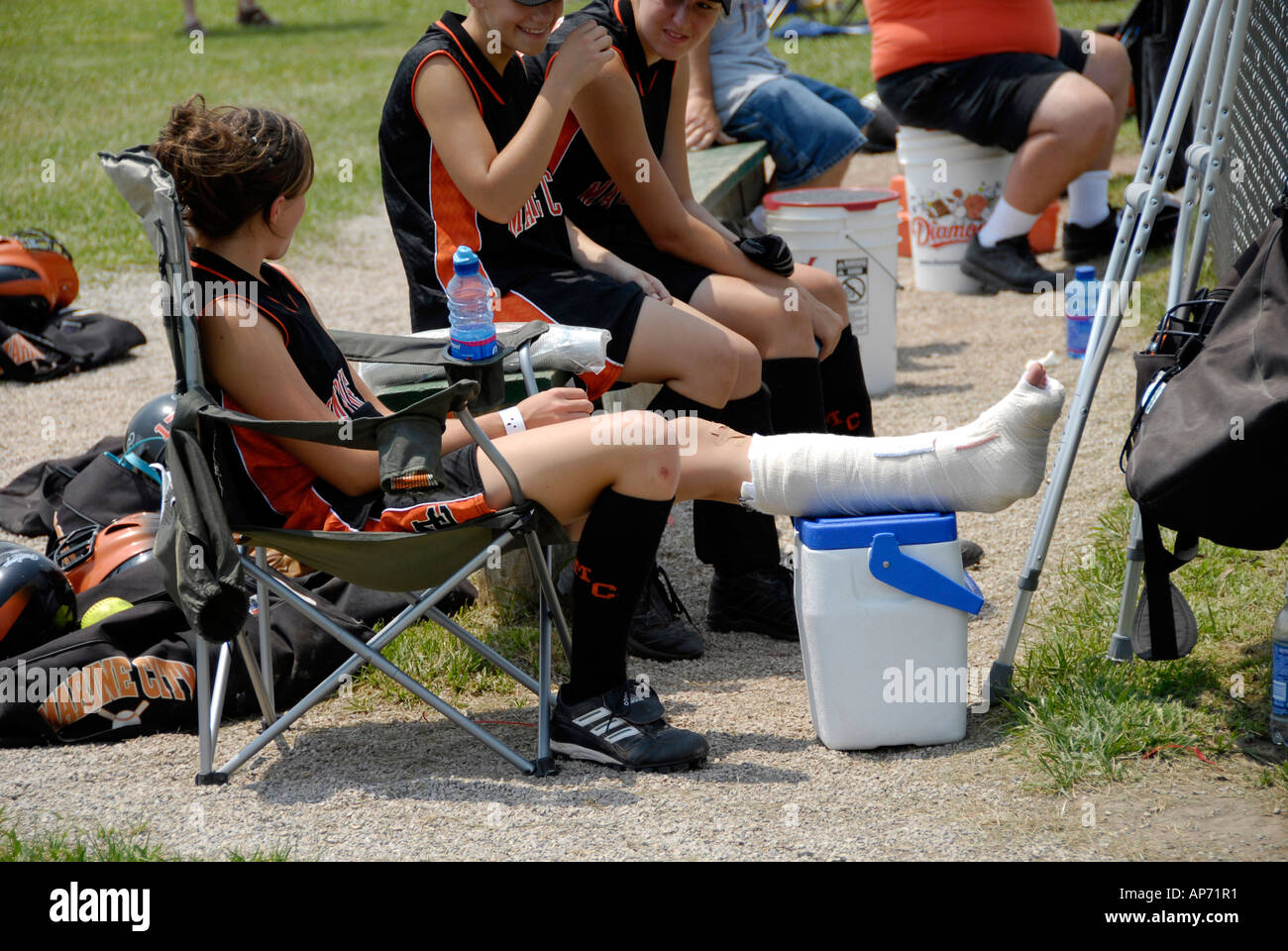Female softball player sprains ankle from Sports injury due to playing baseball Stock Photo