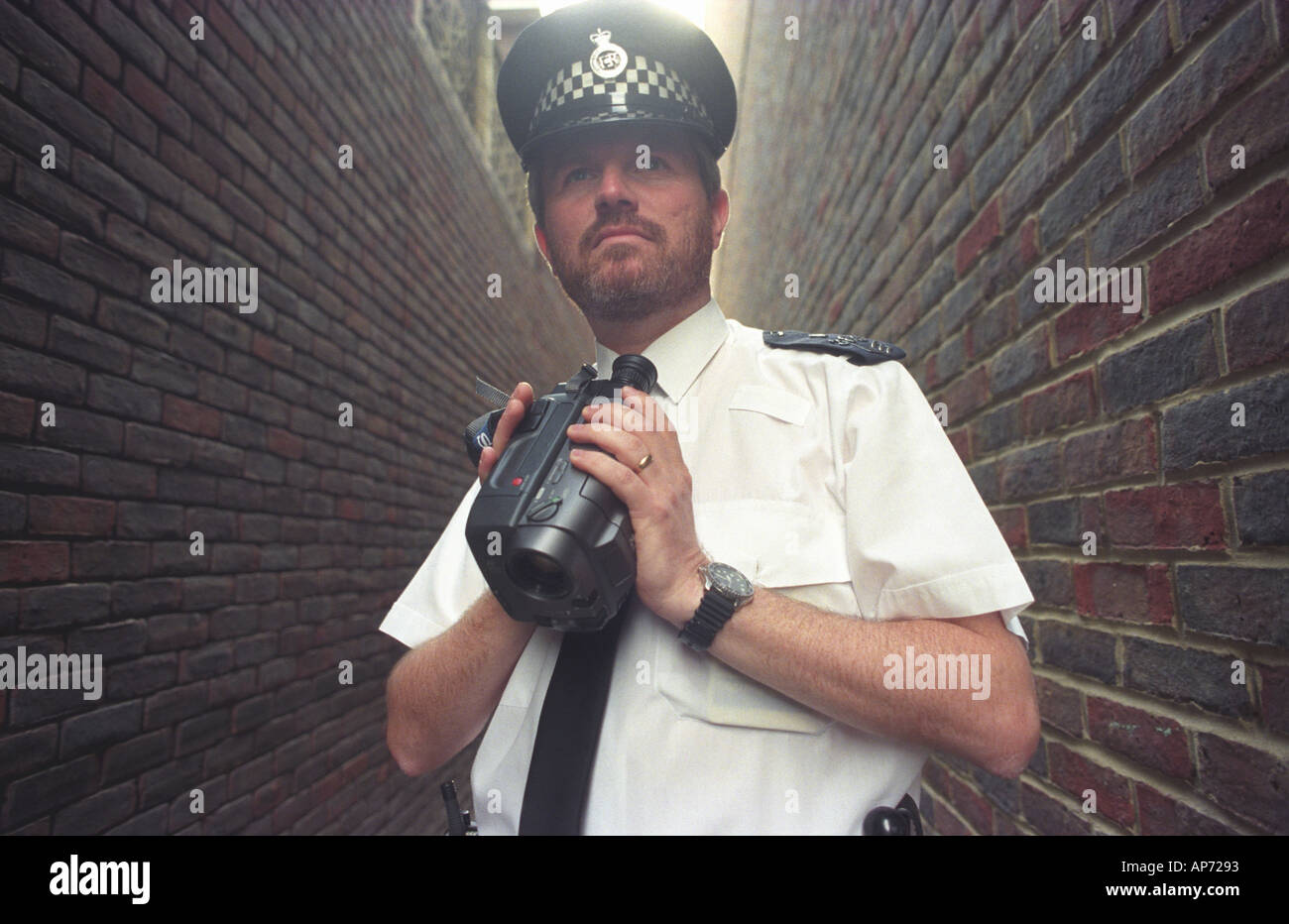 British policeman monitoring events with a video camera Picture by Andrew Hasson 1997 - Stock Image