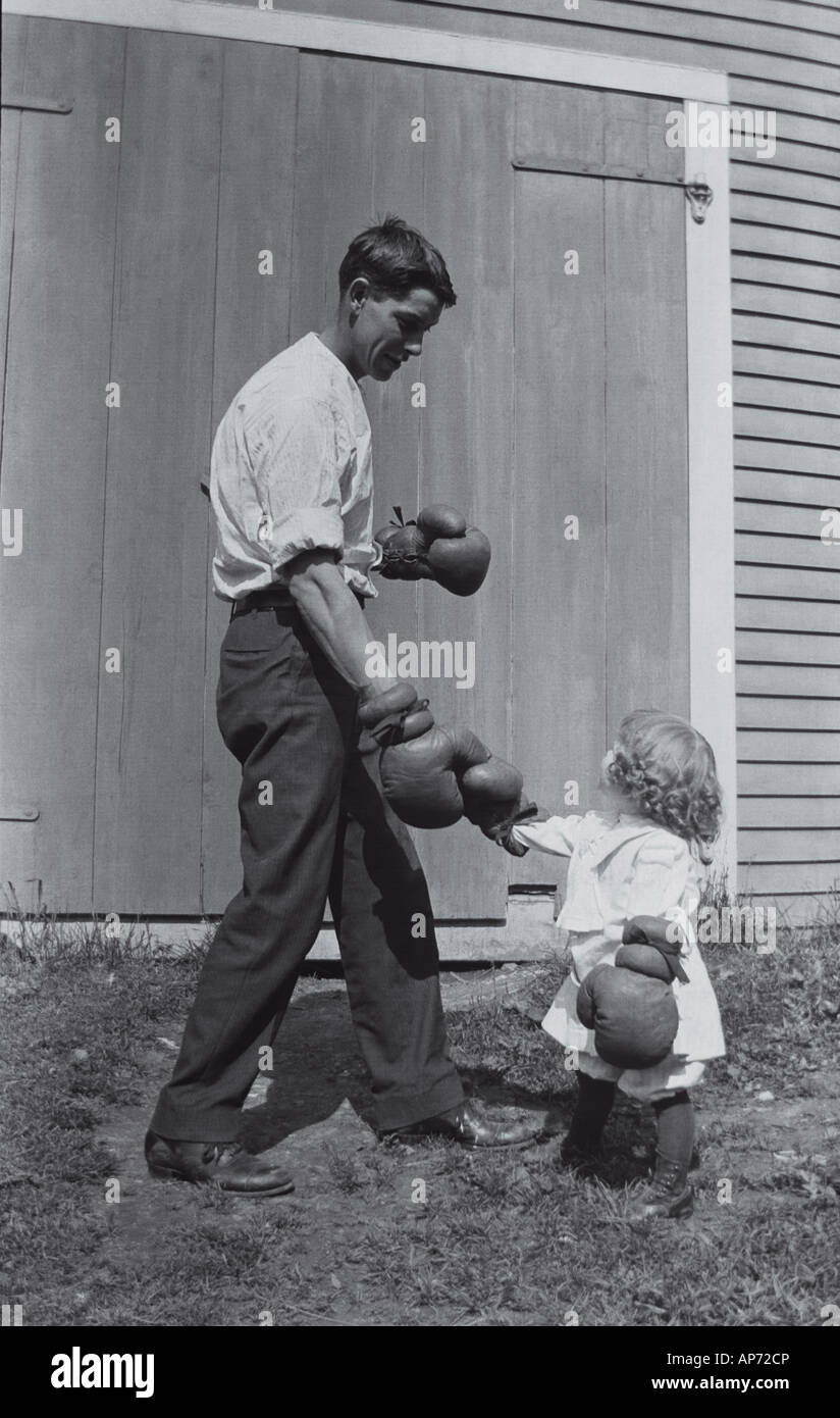 Young man and toddler girl shaking hands with boxing gloves