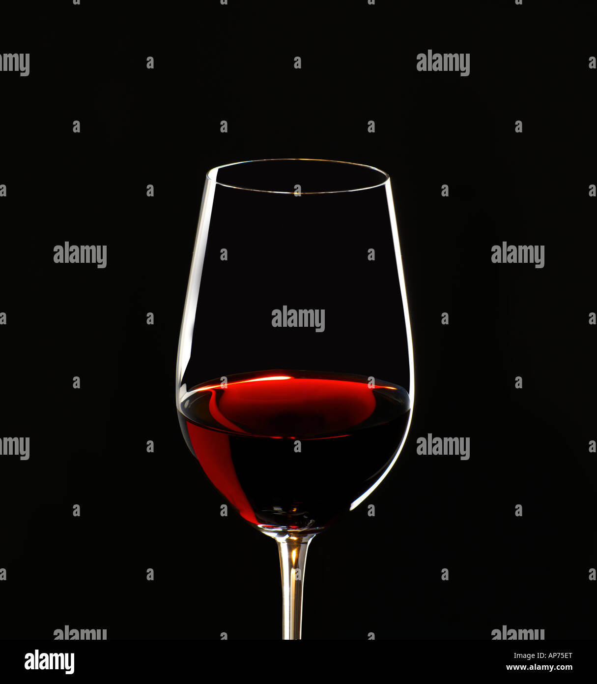 red wine in glass tilted back to show the hues and colours of the ageing process - Stock Image