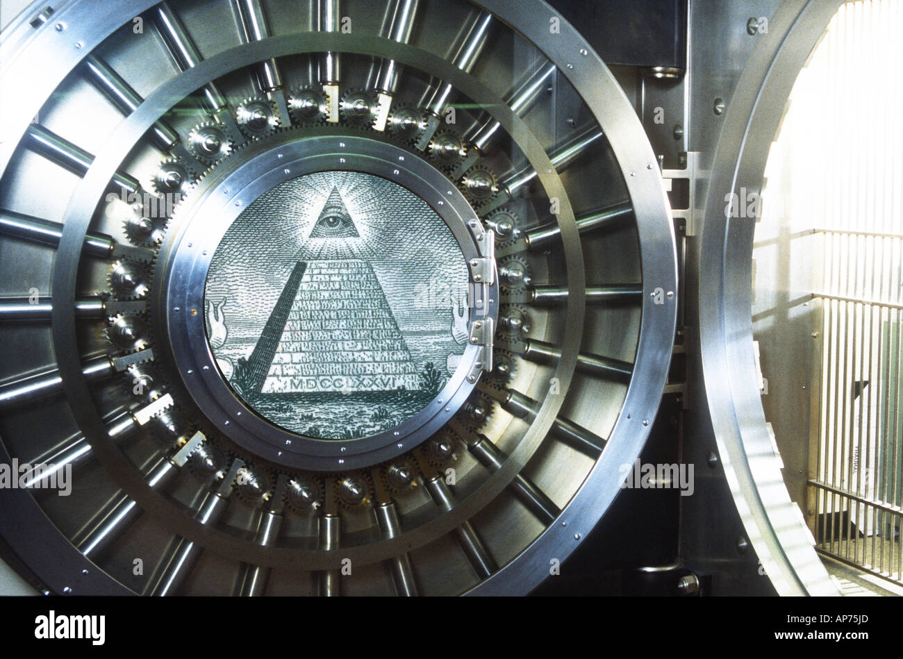 heavy steel round vault door in bank with US dollar pyramid symbol composited on door - Stock Image