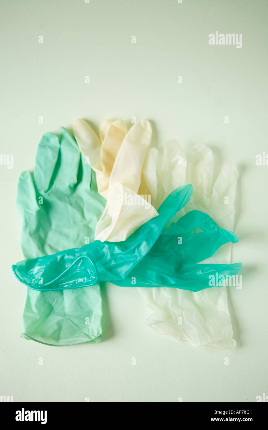 four medical latex gloves green and white in still life clean sterile HIV aids medical vertical biotech - Stock Image