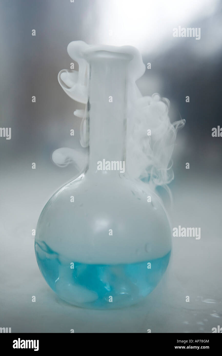 science research chemistry flask with blue solution and smoke in laboratory vertical biotech - Stock Image