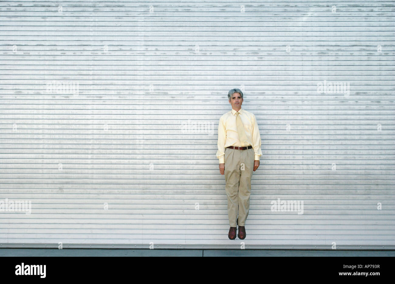 caucasian man jumps in the air with arms at sides next to a gray wall - Stock Image