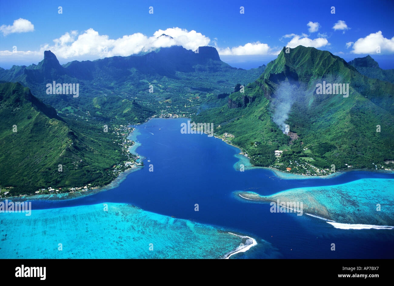 Aerial view of Cooks Bay and mountains on Island of Moorea swimming between blue skies and blue lagoons - Stock Image