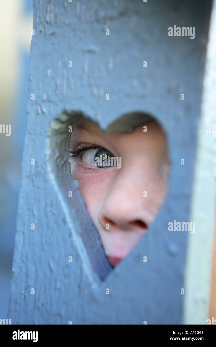 Two year old boy looking out heart shaped hole - Stock Image