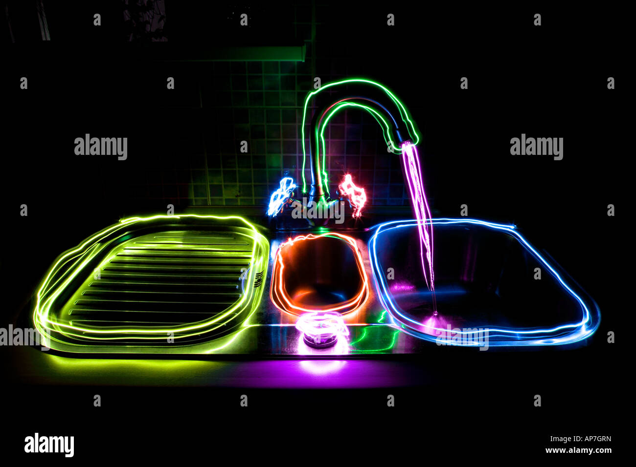 kitchen sink with taps painted with multi colored lights - Stock Image
