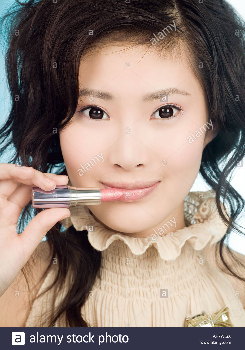 Chinese woman applying lipstick - Stock Image