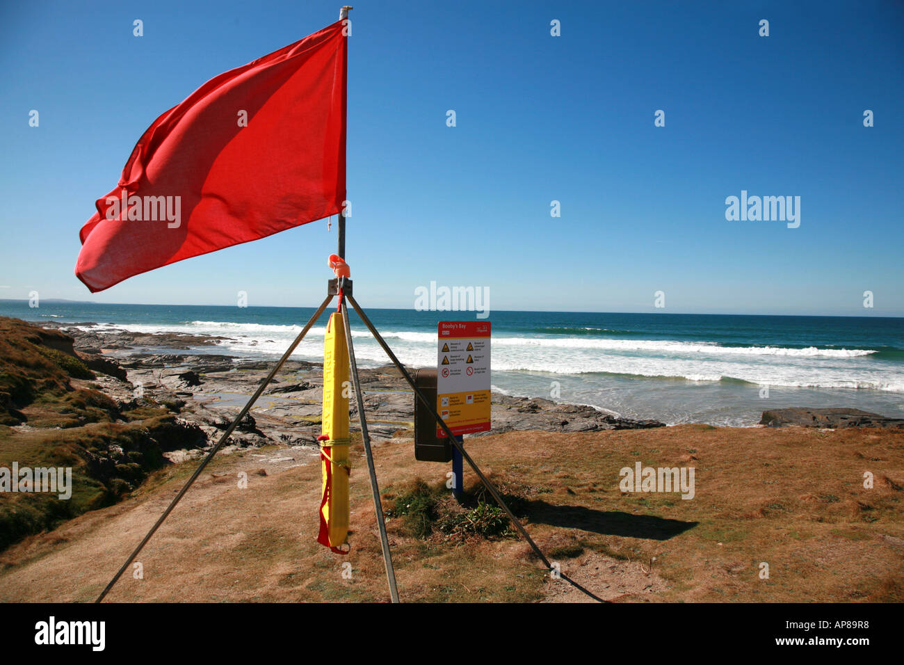 Red flag flying at Booby's Bay on the North Cornish Coast - Stock Image