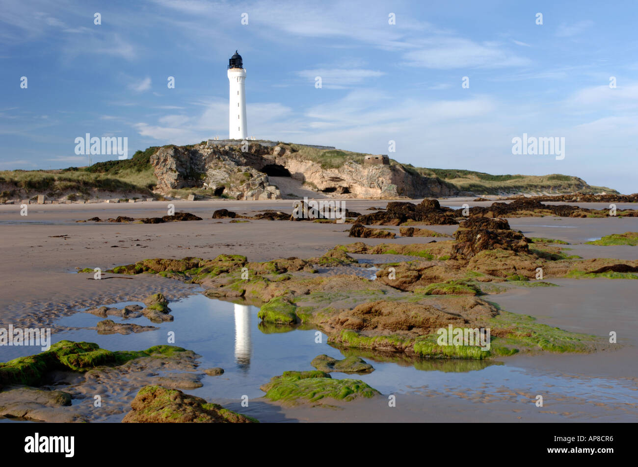Covesea Skerries Lighthouse reflected in rockpools at West Bay, Lossiemouth. Moray. XPL 3443-337 - Stock Image