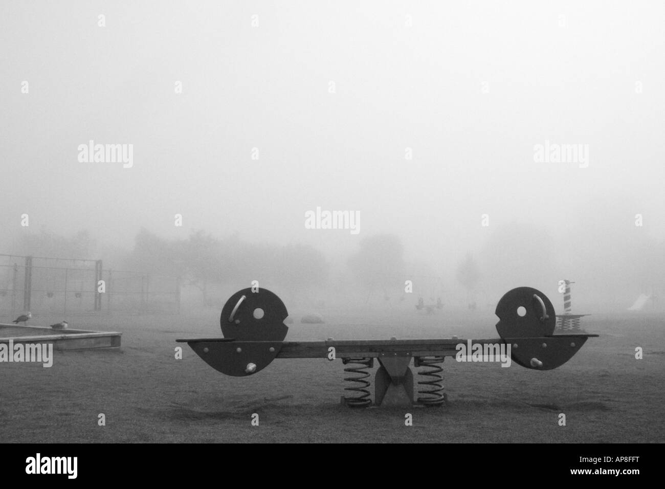 Empty playground on a foggy morning - Stock Image