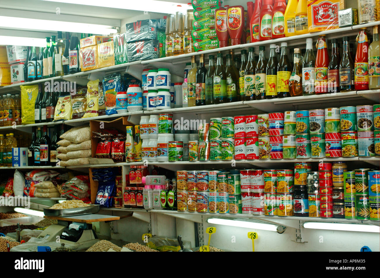 Israel Tel Aviv Lewinski market bottles tins and packets of food for sale at a small grocery store - Stock Image
