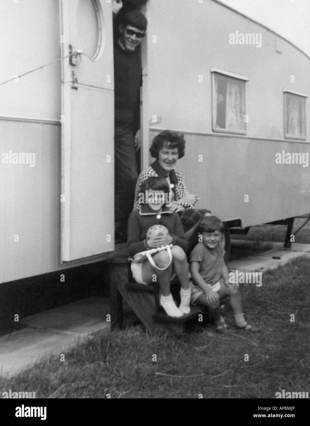 Old black and white family photograph snap shot portrait of mother and her children sat outside a caravan circa 1950