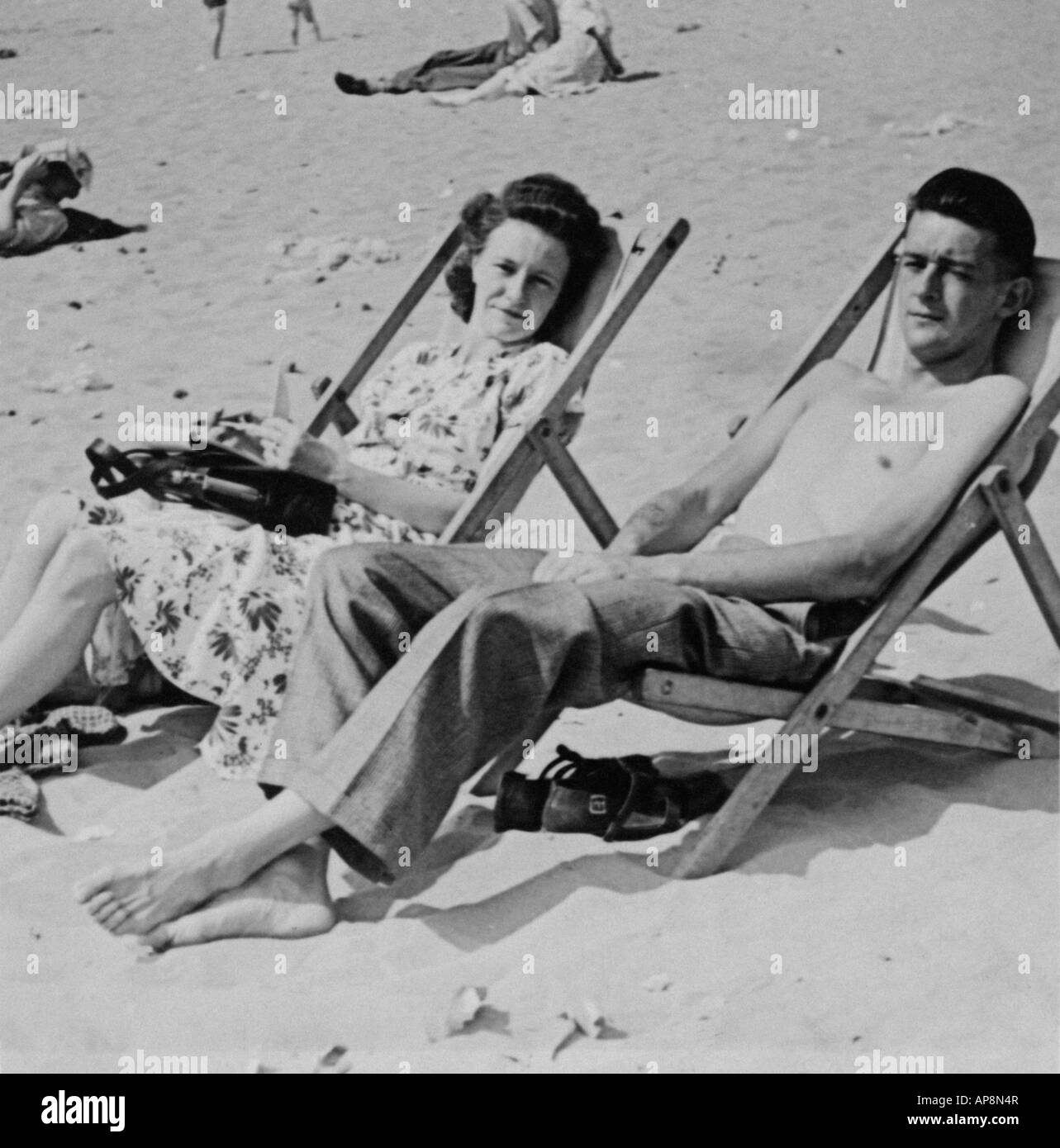 Old black and white family photography snap shot of couple sitting in deck chairs on beach