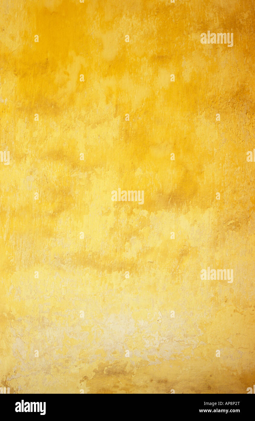 Detail of wall painted in patchy and worn creamy yellow bathed in ...