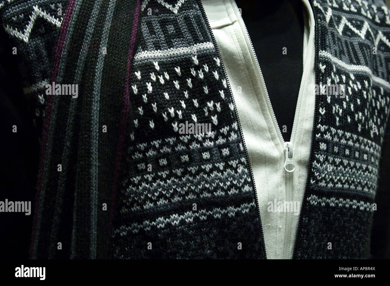 Gray and white patterned sweater, gray and burgundy scarf, white zippered shirt over a black pullover shirt - Stock Image
