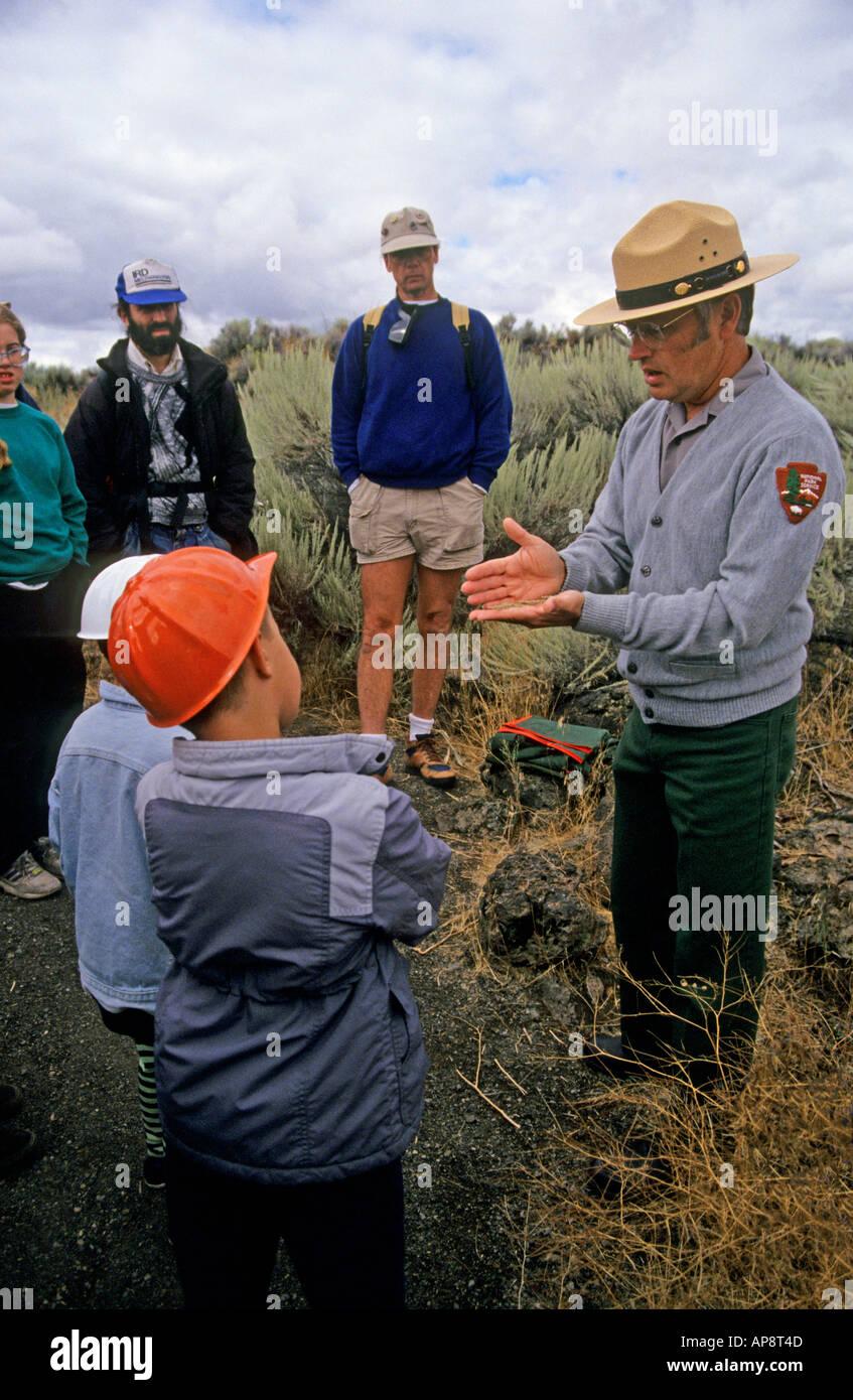 Park ranger explaining environment to children during a hike