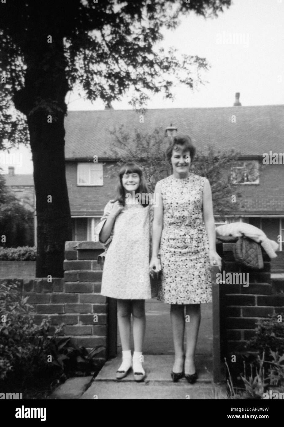Old black and white family photograph snap shot portrait of mother and daughter stood outside their house circa 1950