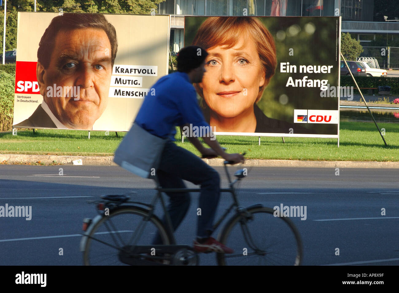 Cyclists passes election campaign posters showing Gerhard Schroeder and Angela Merkel, 2002 - Stock Image
