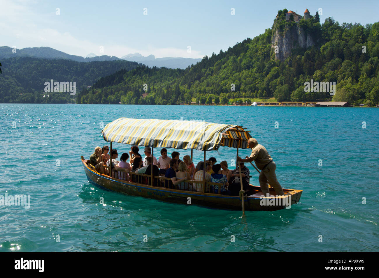 Traditional boats called pletnas on Lake Bled Slovenia with view to Bled Castle - Stock Image