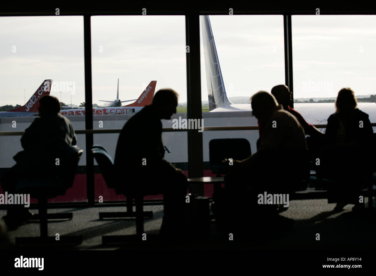 Passengers waiting in lounge in front of window at Belfast International airport northern ireland - Stock Image
