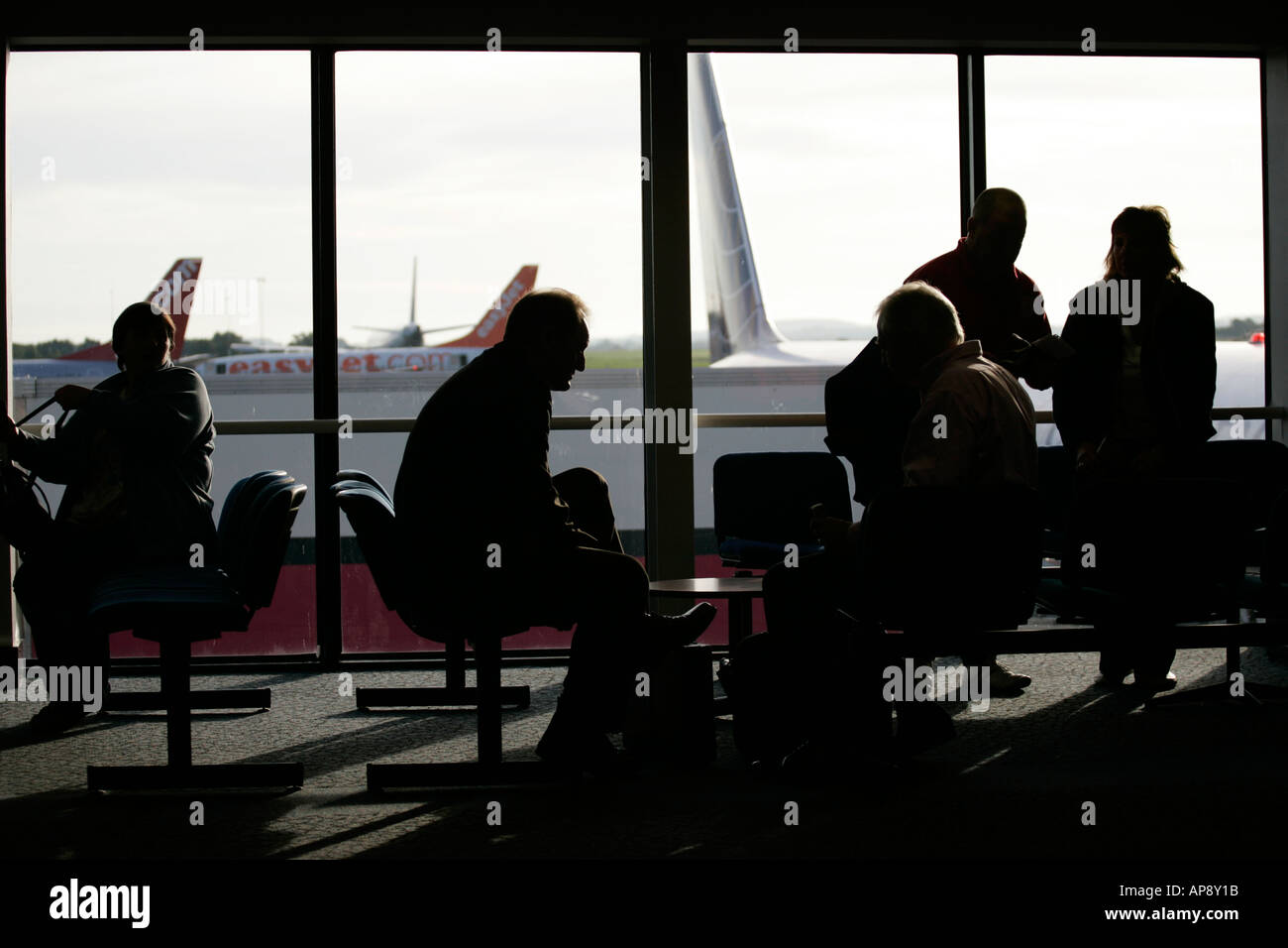 Passenger waiting in lounge in front of window at Belfast International airport northern ireland - Stock Image