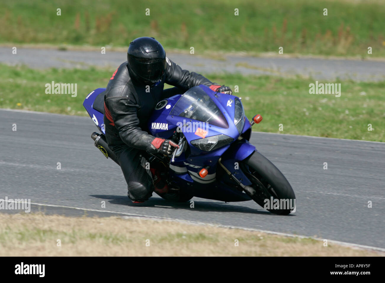rider in black leathers black helmet on blue yamaha R1 with knee down during trackday at Kirkistown circuit - Stock Image