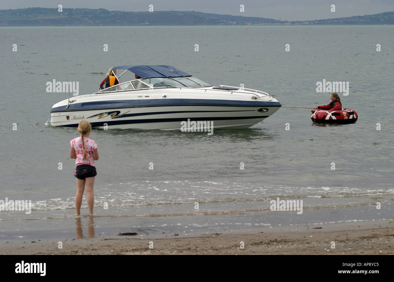 Family with powerboat and inflatable ring enjoy the sea off Ballyholme beach bangor county down - Stock Image