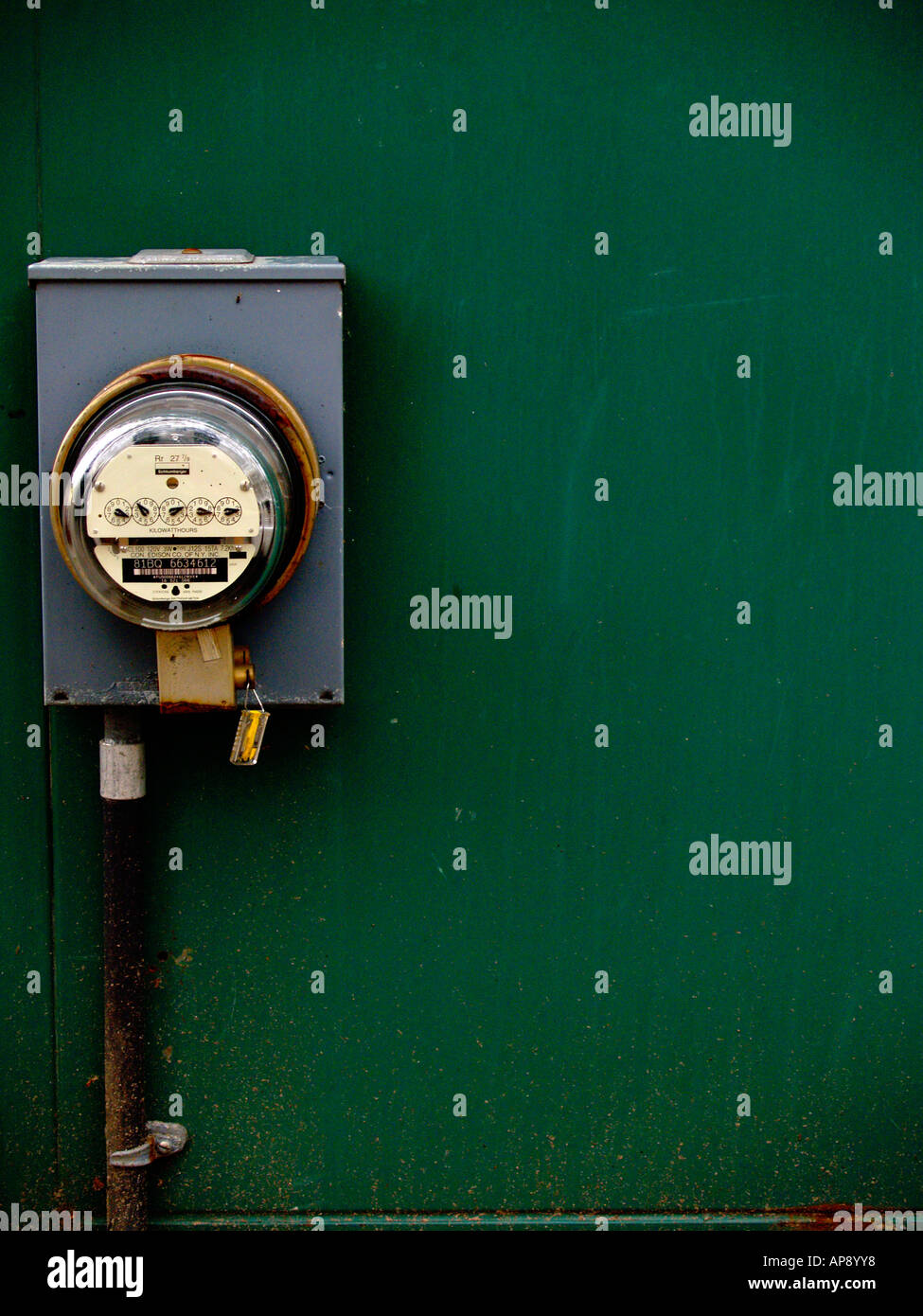 Outdoor electrical power meter at left side of frame on blue-green wall with slight vignetting. - Stock Image