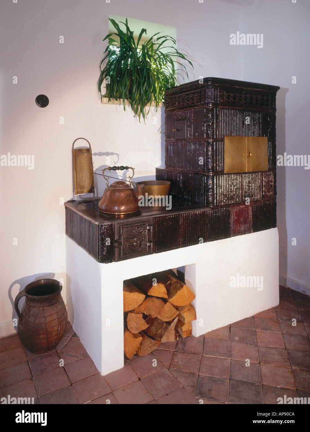 Traditional tiled stove inside house - Stock Image