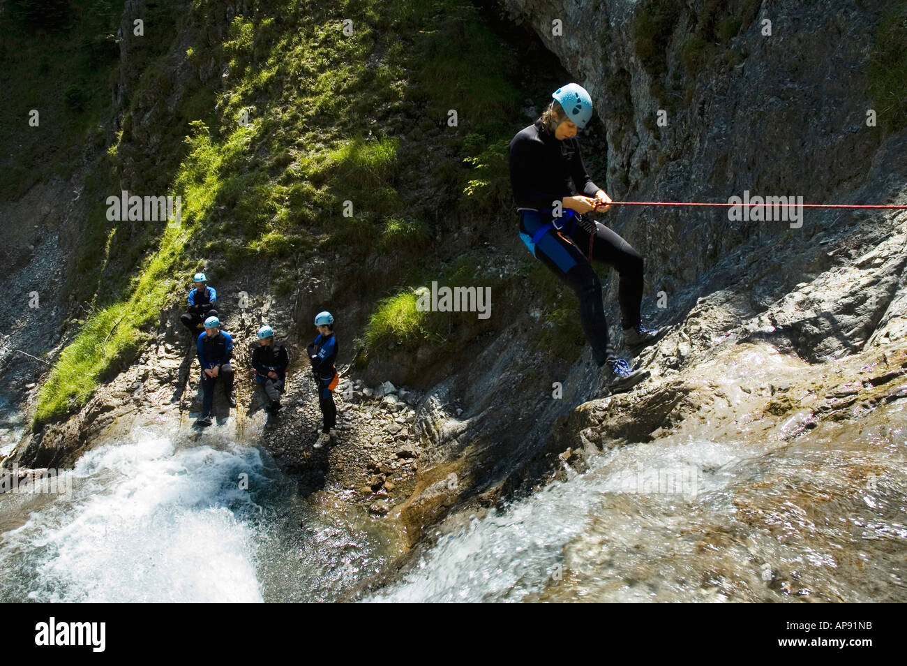 Abseiling down a waterfall on a canyoning trip in the Lechtal in the Austrian Tirol - Stock Image