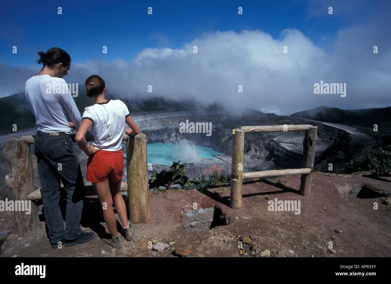 Young couple looking into the steaming crater of active Poas Volcano, Parque Nacional Volcan Poas, Costa Rica - Stock Image