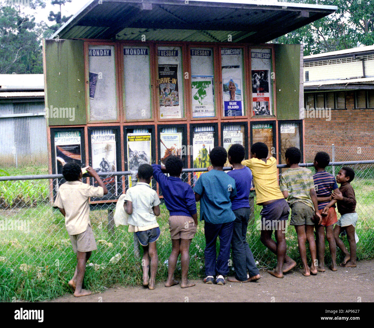 Barefoot children and western film posters Papua New Guinea - Stock Image