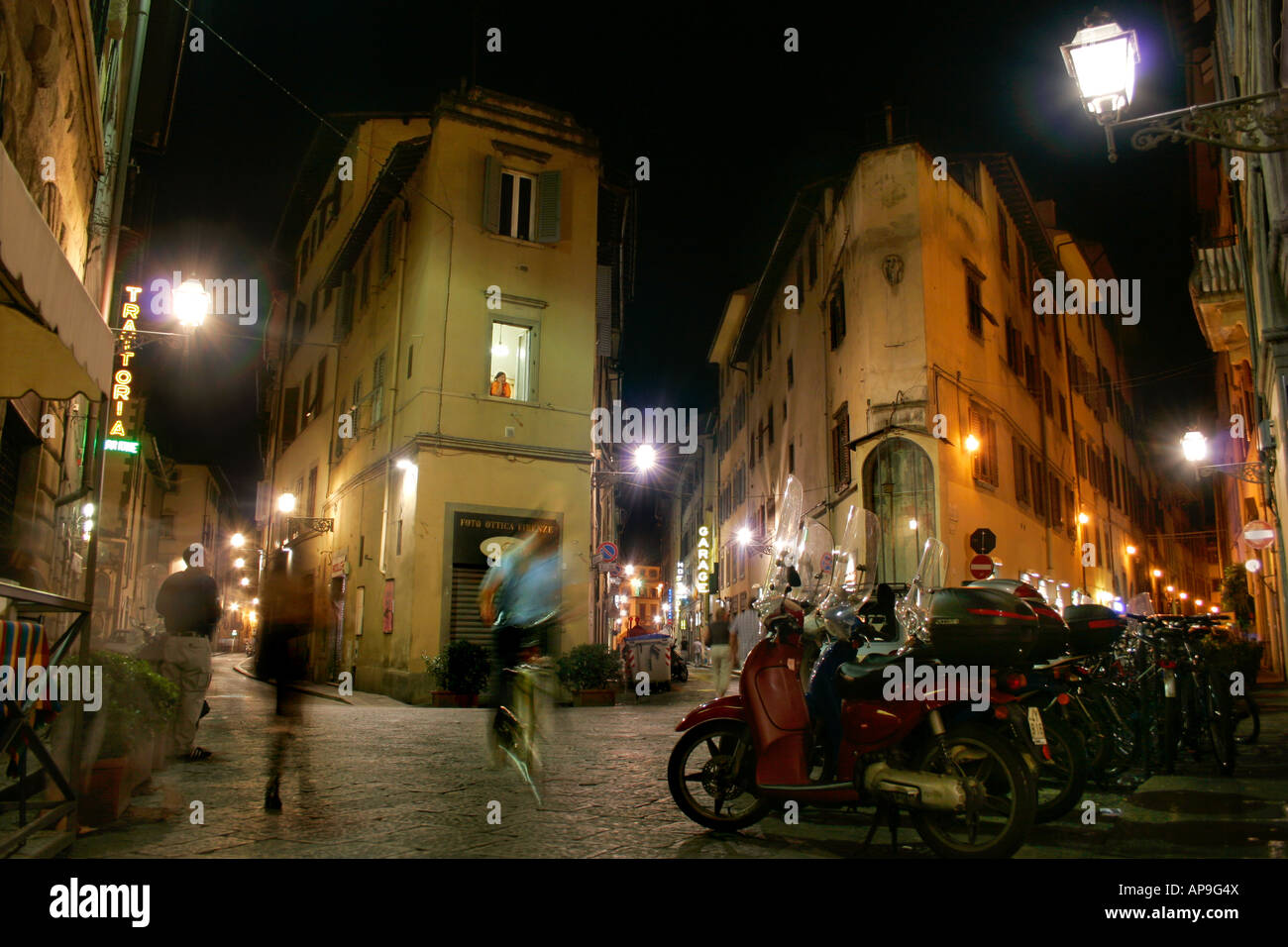 a lively and atmospheric alley lane at night in Florence | atmosphärisch dichte, belebte Gasse nachts in Florenz - Stock Image