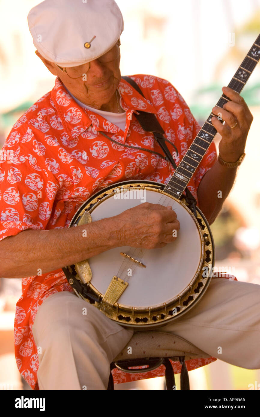 An active senior enjoys playing the banjo in a jazz band - Stock Image