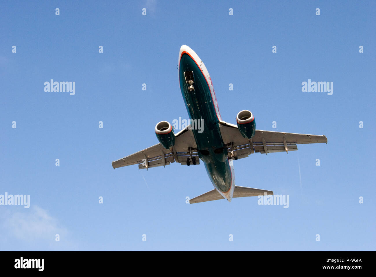 A commercial airliner flying overhead with blue sky above. - Stock Image