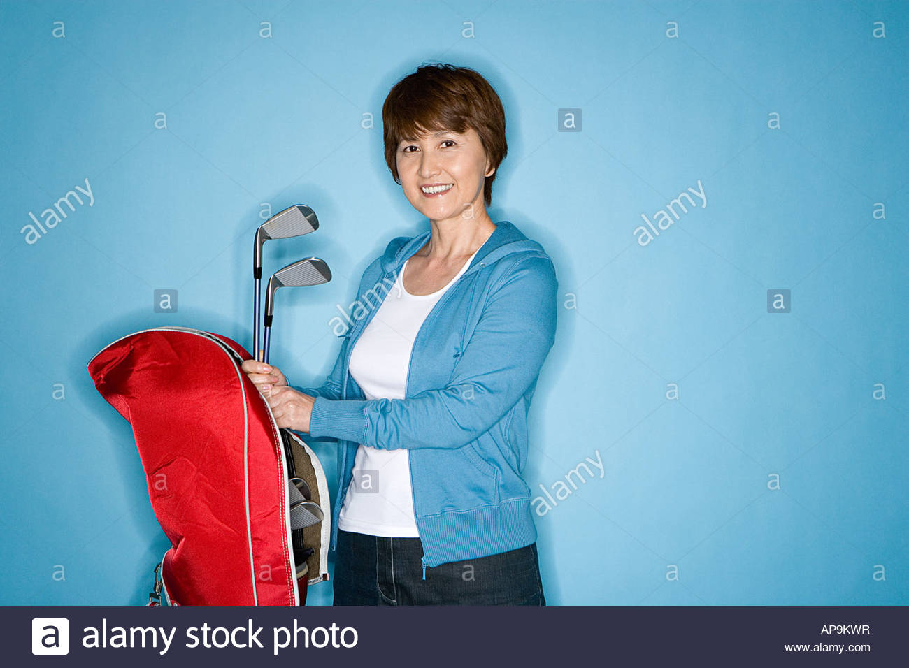 Woman with golf clubs - Stock Image