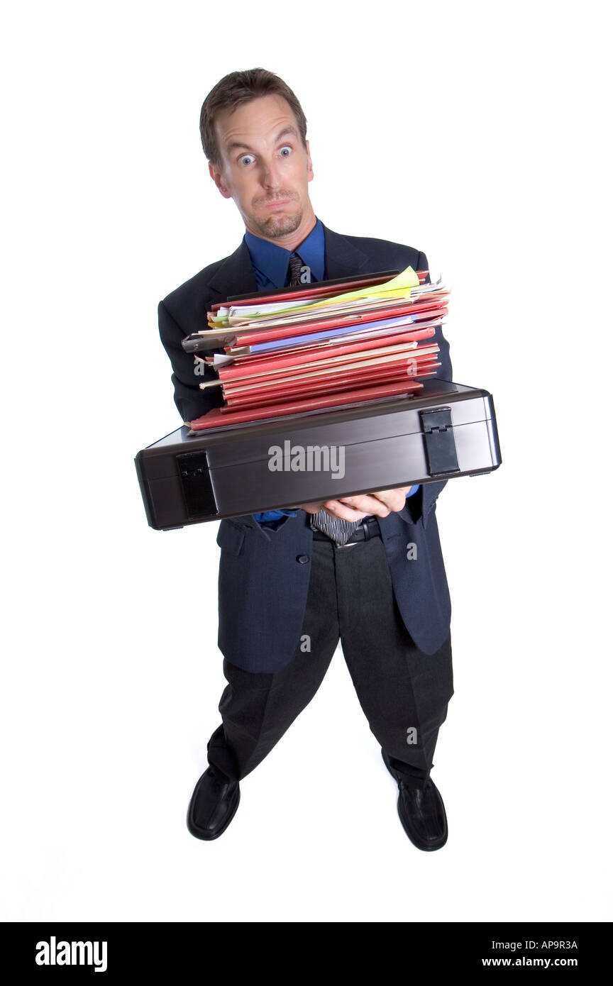 Overworked businessman tipping over from carrying too many folders - Stock Image