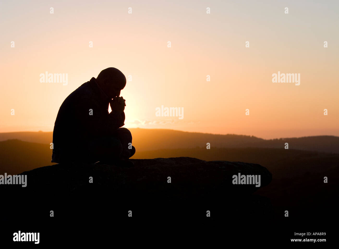 Silhouette profile of a man sat thinking on a hill at sunrise - Stock Image