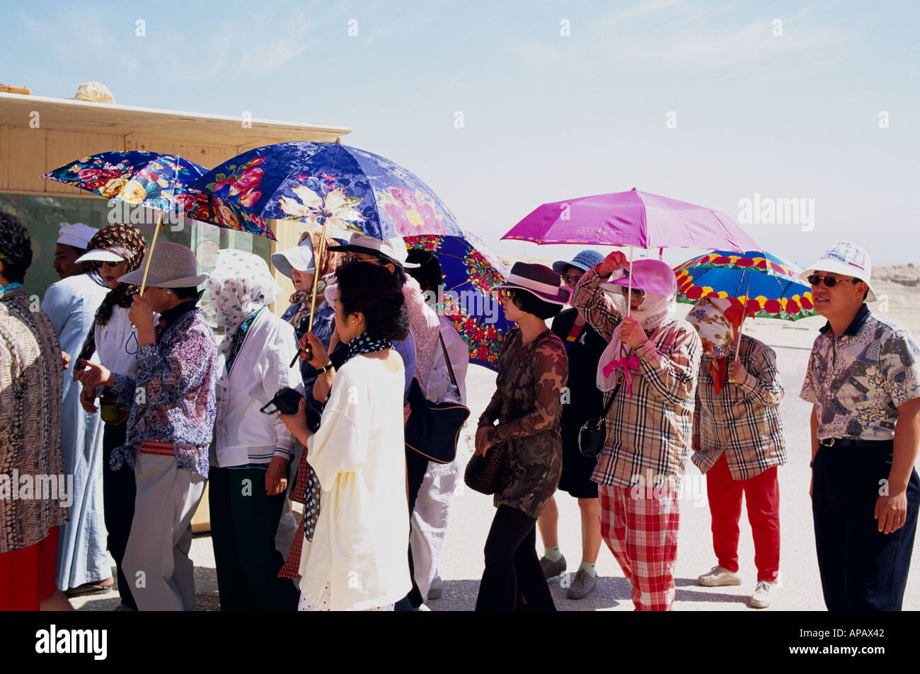 Japanese Tourists With Umbrellas The Valley Of The Kings  Egypt North Africa Stock Photo