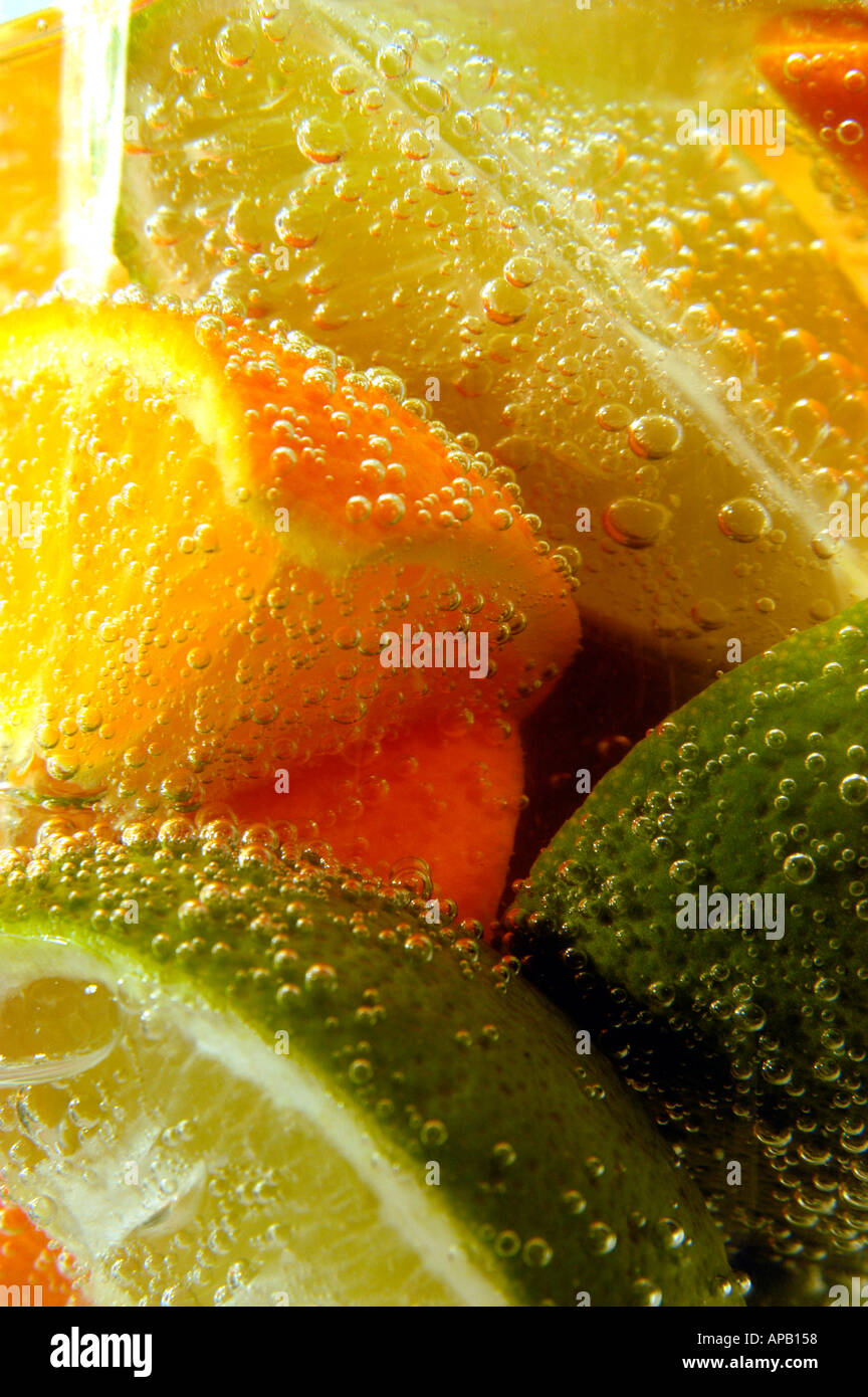 Oranges and limes in bubbly water - Stock Image
