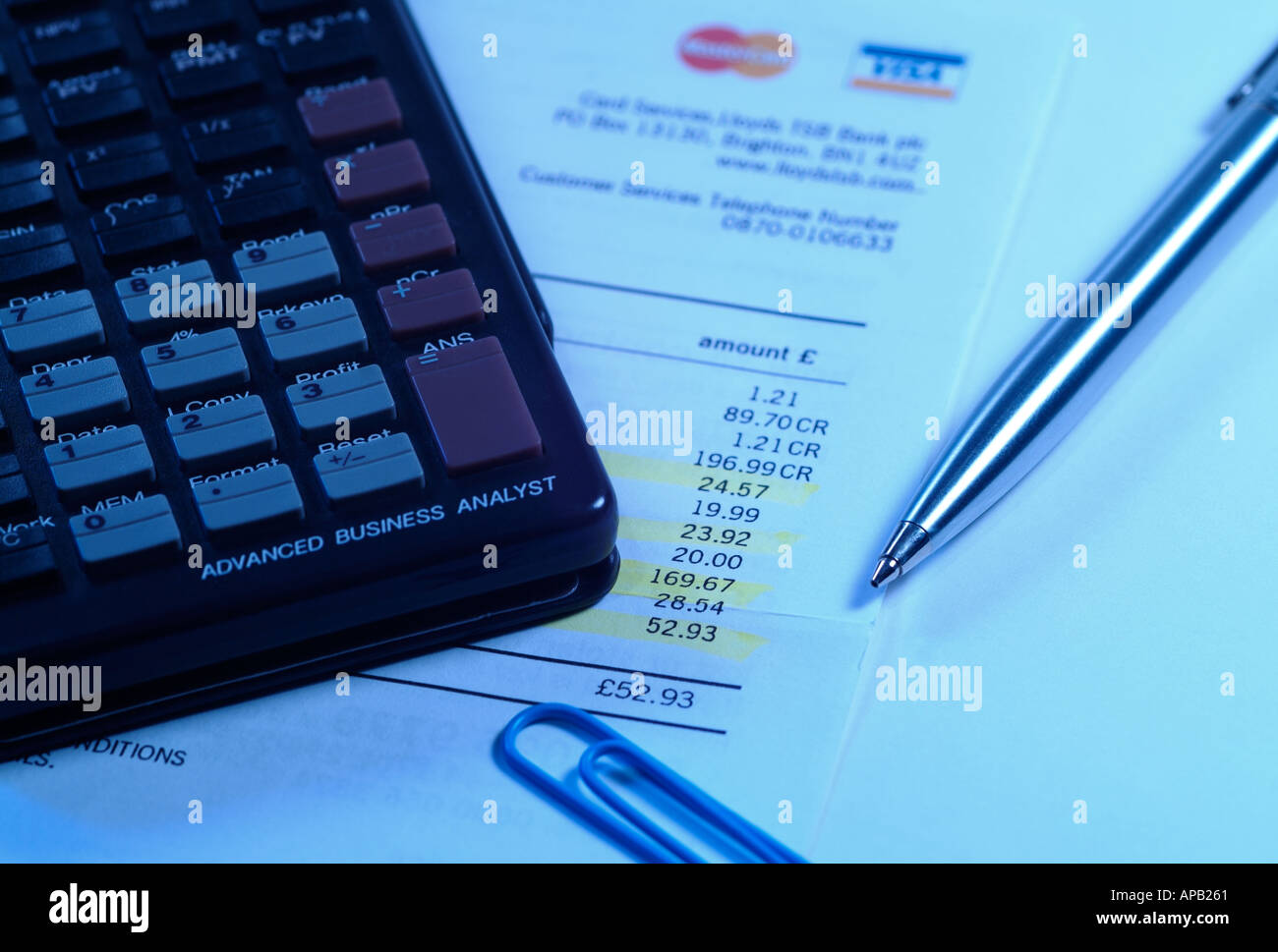 Personal Finance Image with a Creditcard Bill, Calculator and Pen. - Stock Image