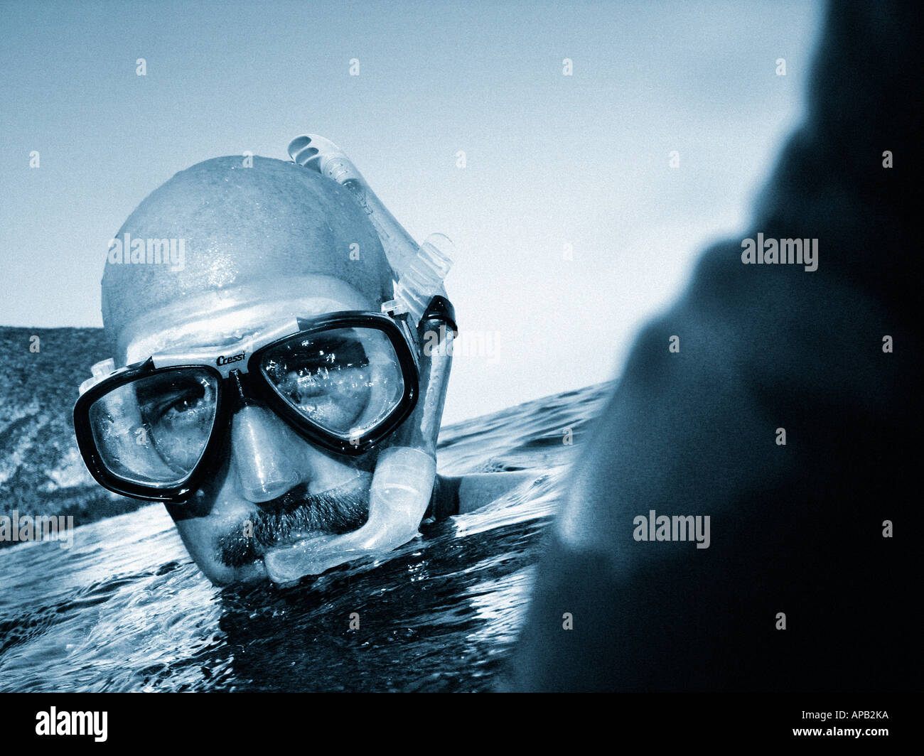 Black and white image of a man snorkelling in the sea - Stock Image