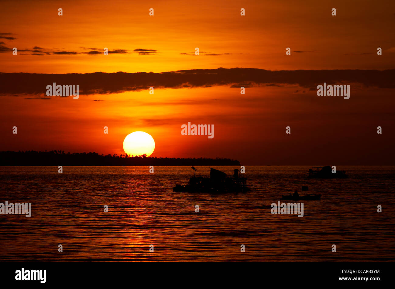 Local fishermen sail out in the early evening to fish the waters around Manado North Sulawesi Indonesia Stock Photo
