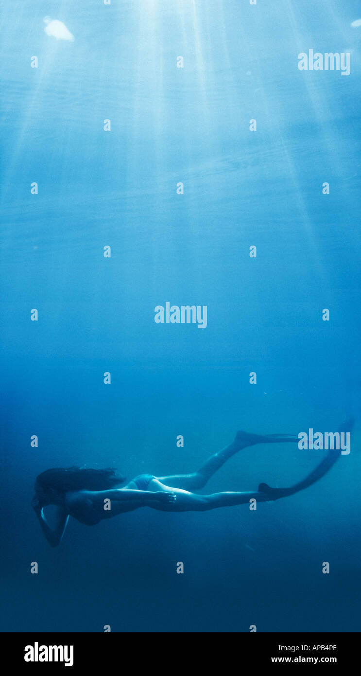 Girl swimming at the bottom of the sea - Stock Image