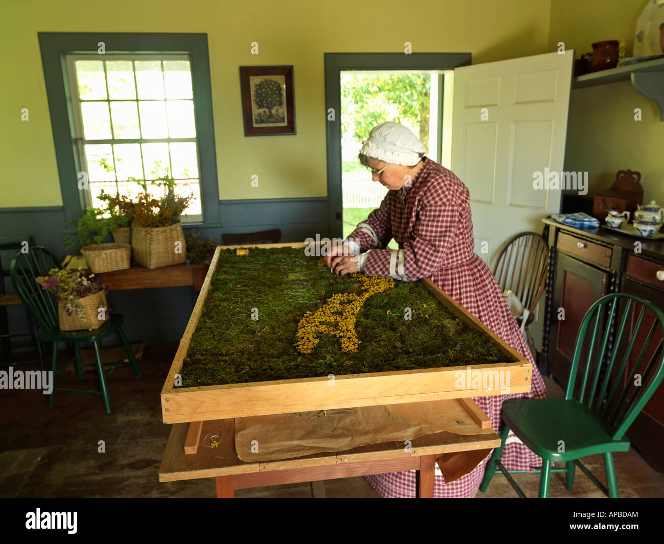 Canada Ontario Morrisburg Upper Canada Village woman creating a tapestry from moss and dried flowers - Stock Image