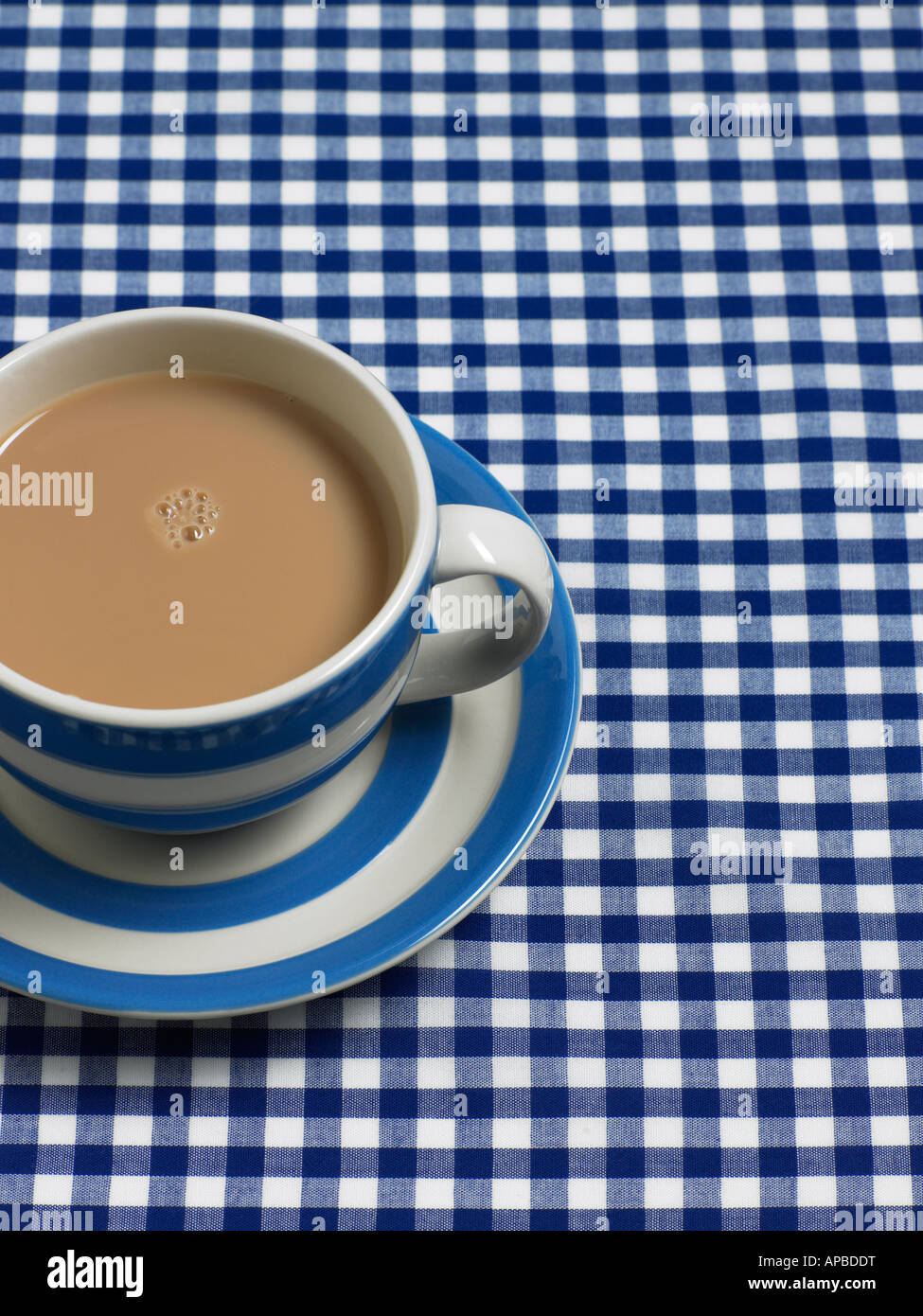 cornish blue stripped tea cup on gingham - Stock Image