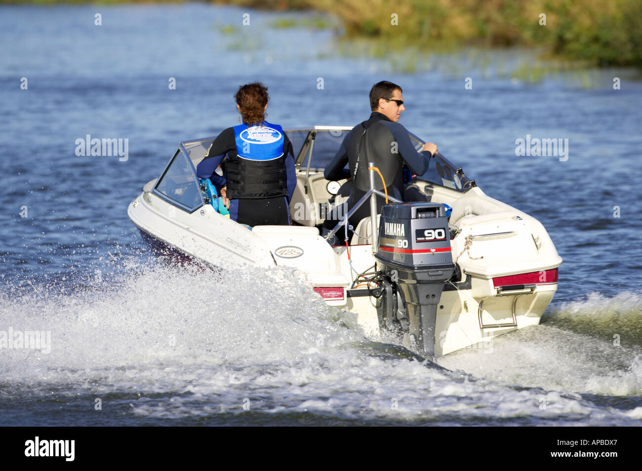 couple in wetsuits on a motor speed boat with yamaha 90 outboard speeding along the river bann county antrim northern ireland - Stock Image