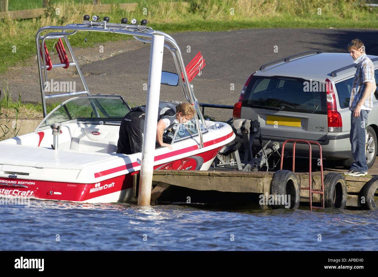 men loading a mastercraft x star wakeboard edition speed boat onto the back of a trailer attached to a volvo estate car on a jet - Stock Image